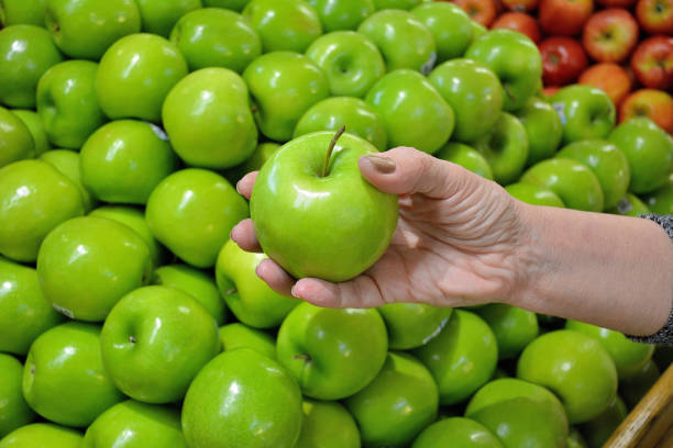 """Lifestyle, """" Green, Granny Smith Apples """" Lifestyle...A customer examines a green """"Granny Smith"""" apple. granny smith apple stock pictures, royalty-free photos & images"""