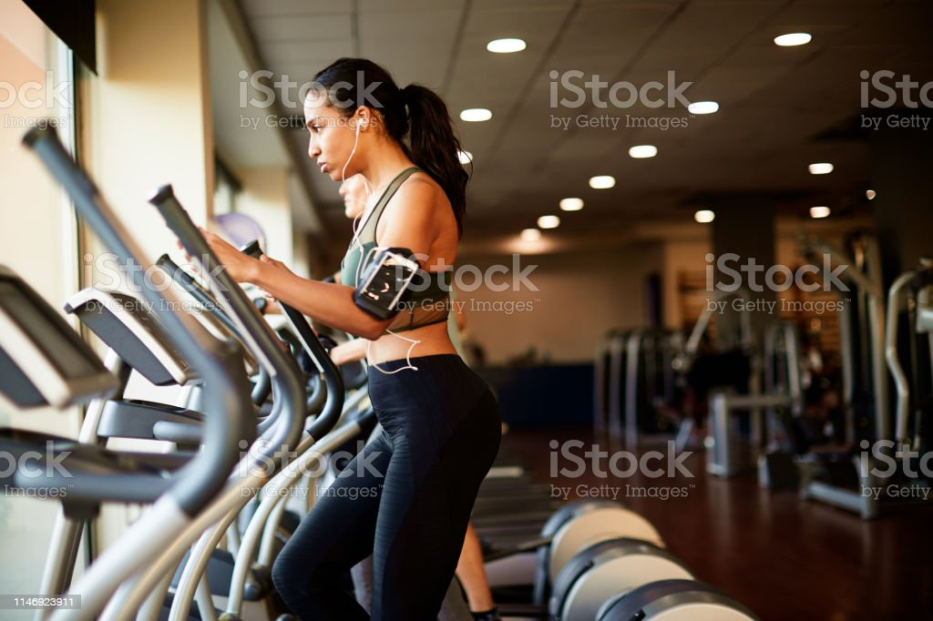 Lifestyle  gym and fitness work out one the elliptical. - Foto stock royalty-free di Abbigliamento sportivo