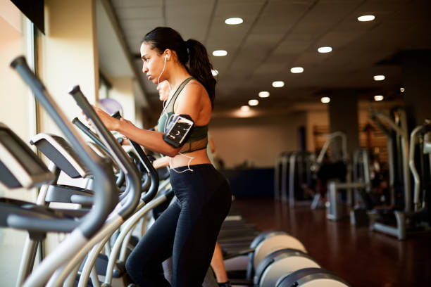 lifestyle  gym and fitness work out one the elliptical. - ellipse stock photos and pictures