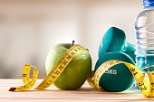 Dumbbells with apple, mineral water bottle and tape measure on wood table and gym background. Concept lifestyle, health, diet and sports. Horizontal composition. Front view