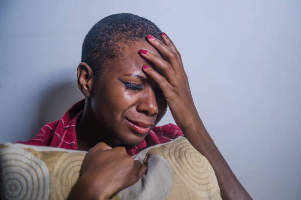 lifestyle indoors shady portrait of young sad and depressed black afro American woman sitting at home floor feeling desperate and worried suffering pain and depression in dramatic light lifestyle indoors shady portrait of young sad and depressed black afro American woman sitting at home floor feeling desperate and worried suffering pain and depression in dramatic light woman crying stock pictures, royalty-free photos & images