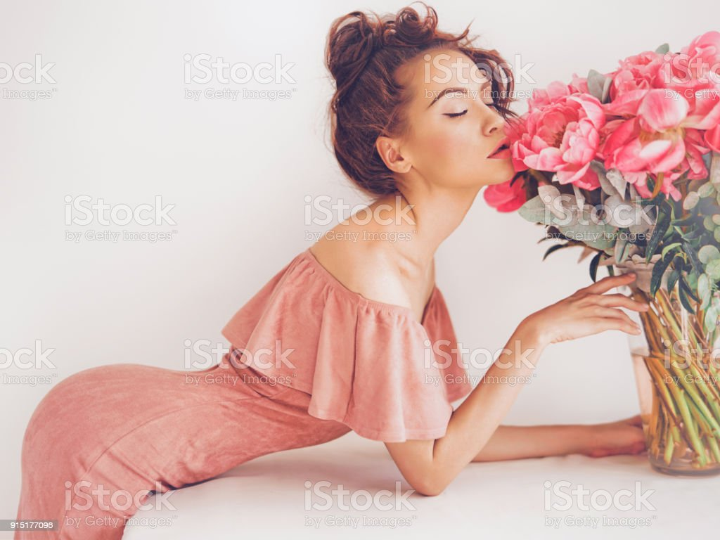 Lifestyle photo of young woman with pink peonies stock photo
