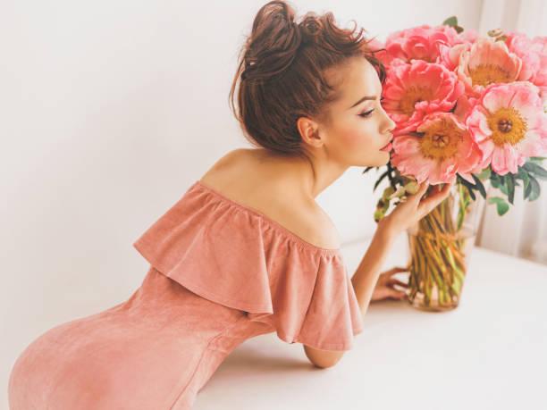 lifestyle-foto der jungen frau mit rosa pfingstrosen - soup_studio stock-fotos und bilder