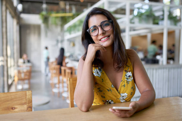 Lifestyle portait of confident beautiful natural brunette hispanic millennial vlogger sitting in modern restaurant smiling at camera stock photo