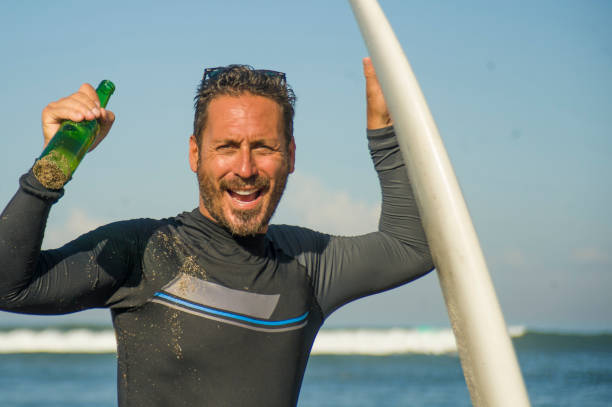 lifestyle-porträt von attraktiven und glücklichen surfer mann 3os bis 40er jahre in neopren-surf-badeanzug posiert mit surfbrett am strand trinken bierflasche genießen wassersport und sommerurlaub - bier gesund stock-fotos und bilder