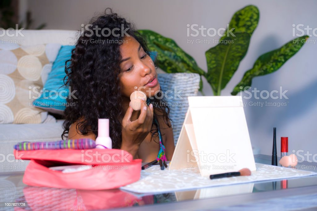 lifestyle portrait of young happy and beautiful latin American woman using sponge beautyblender spon applying face makeup base foundation concealer looking at mirror in female beauty skin care stock photo