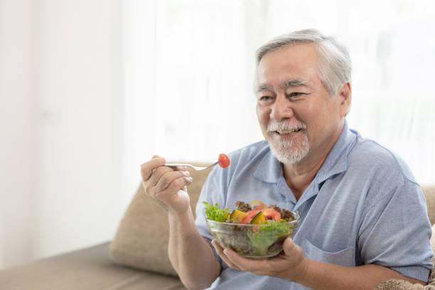 Lifestyle senior man feel happy enjoy eating diet food fresh salad on sofa stock photo