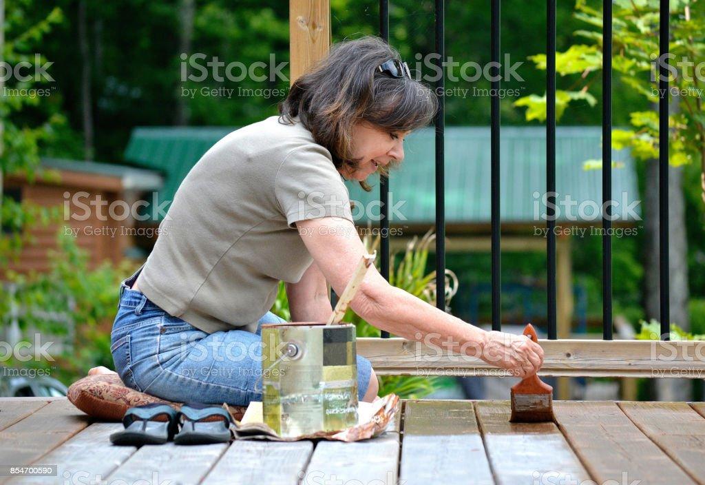 Lifestyle, Senior woman, 50+, paints a deck. stock photo