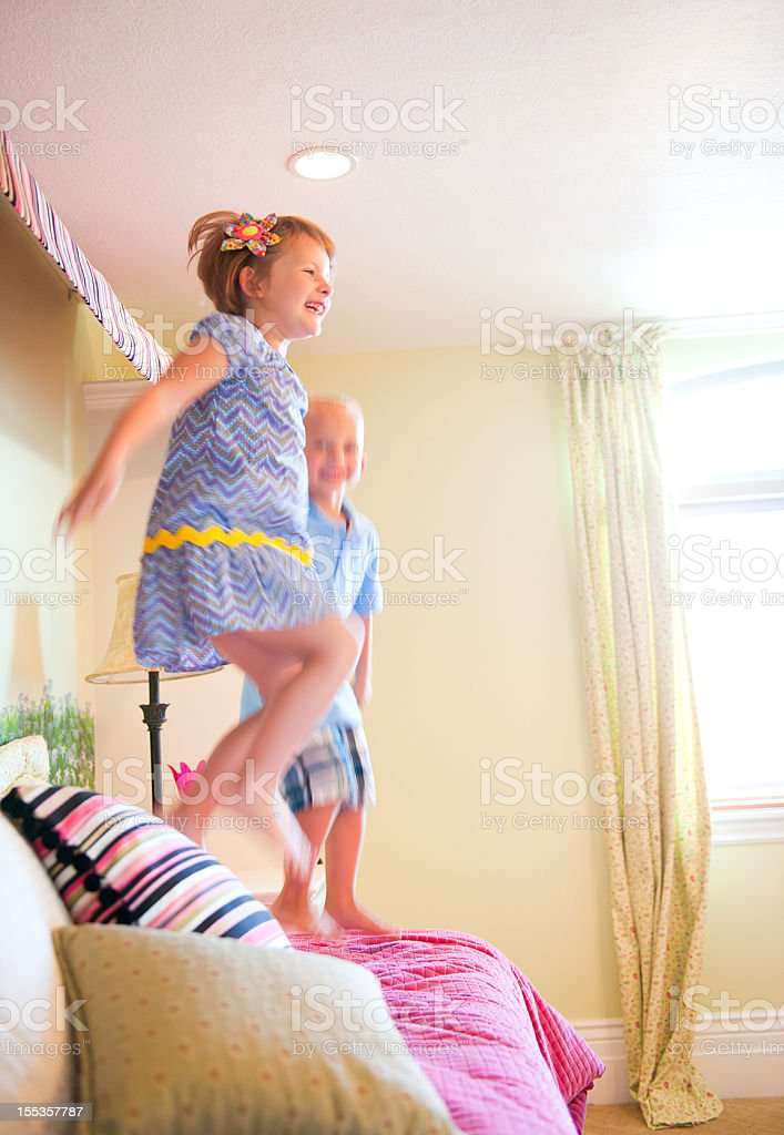 Lifestyle Series: Adorable Children Jumping on the Bed stock photo
