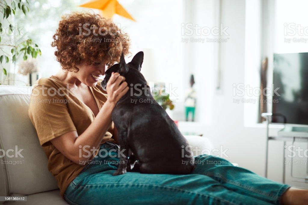 Lifestyle-Frau mit eine französische Bulldogge im Wohnzimmer entspannen. – Foto