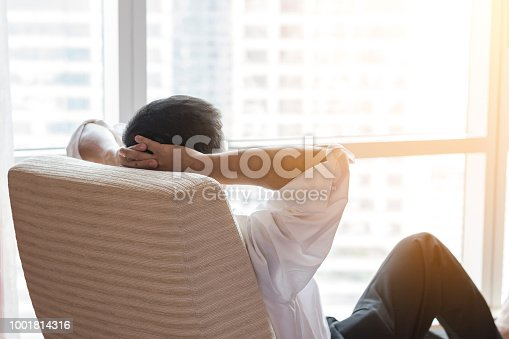 istock Life-work balance and city living life style concept of business man relaxing, take it easy in office room resting with thoughtful mind thinking of lifestyle quality looking forward to urban scene 1001814316