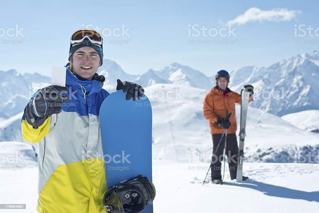 Two man with winter sport equipment looking at camera. One is showing...
