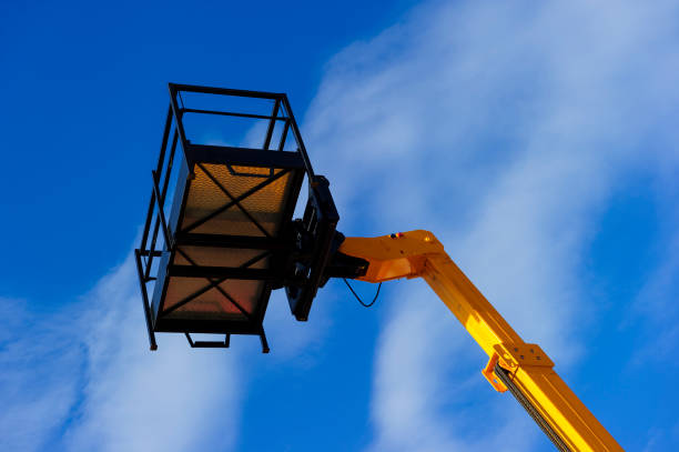 Lift platform with bucket Hydraulic lift platform with bucket of yellow construction vehicle, heavy industry, blue sky and white clouds on background mobile crane stock pictures, royalty-free photos & images