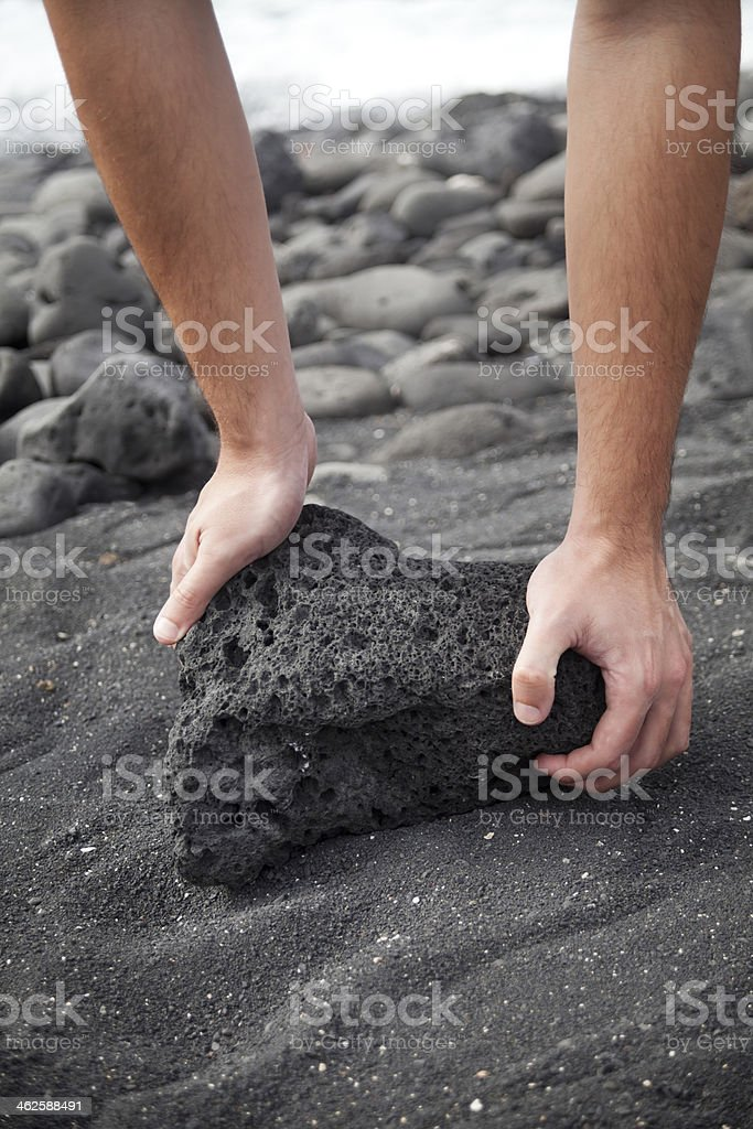 Lifting a volcanic stone stock photo