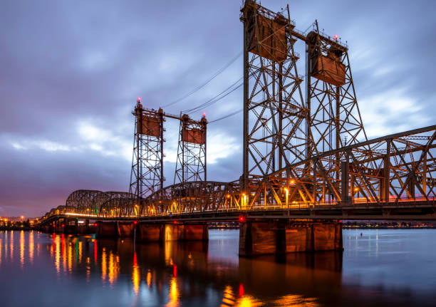 Lifting Columbia Interstate bridge over the Columbia River connecting Oregon and Washington and shines with colorful evening lights Drawbridge arched truss Columbia Interstate bridge over the Columbia River with evening lights with lift towers for lifting the bridge section for the passage of vessels connect Oregon and Washington bascule bridge stock pictures, royalty-free photos & images