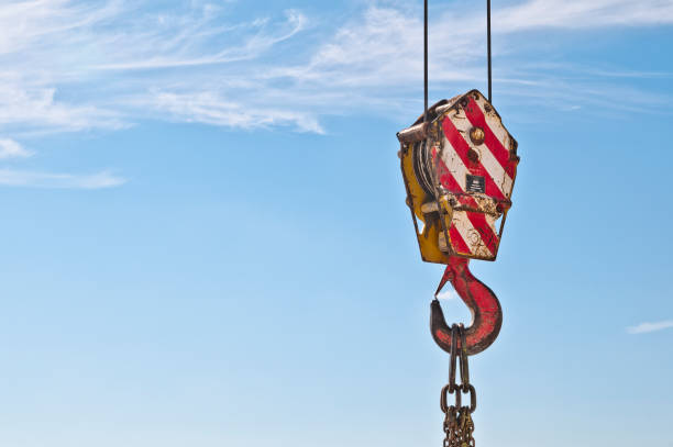 Lifting hook crane and chain links. Lifting hook for heavy loads. Tower  lifting  crane with steel hook building metal construction against clear blue sky. Hook a crane old rusty and high construction and chain links rigging stock pictures, royalty-free photos & images