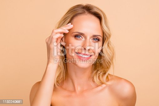istock Lifting therapy treatment concept. Close-up portrait of her she attractive cheery wavy-haired nude lady with flawless perfect smooth pure shine skin touching forehead isolated over beige background 1132240681
