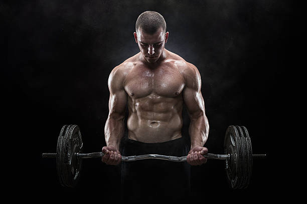 Lifting weights Close up of young muscular man lifting weights over dark background macho stock pictures, royalty-free photos & images