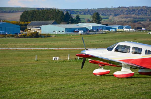 Light Aircraft Parked on Grass Air Strip stock photo