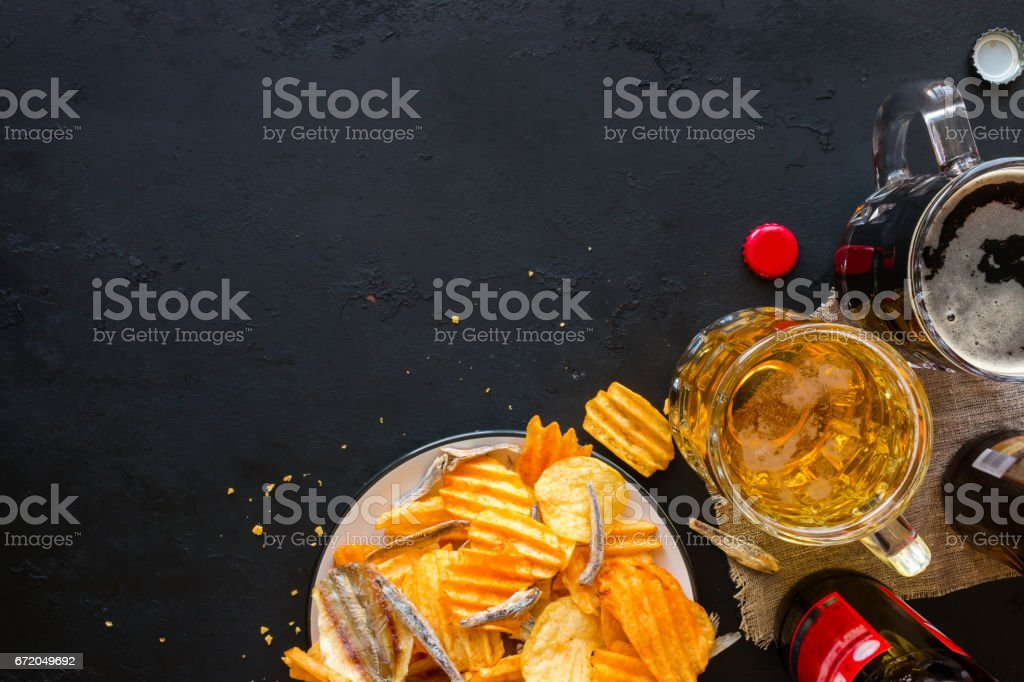 Light and dark beer with a snack of chips and fish on a black background mockup stock photo