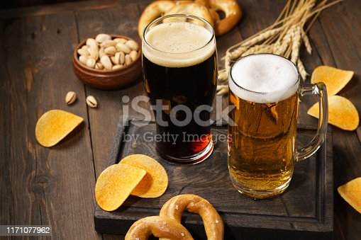 istock Light and dark beer with various snacks on a wooden background. 1171077962