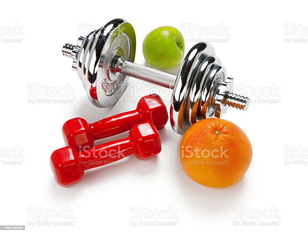 Light and Heavy dumbbells with green apple ang grapefruit stock photo
