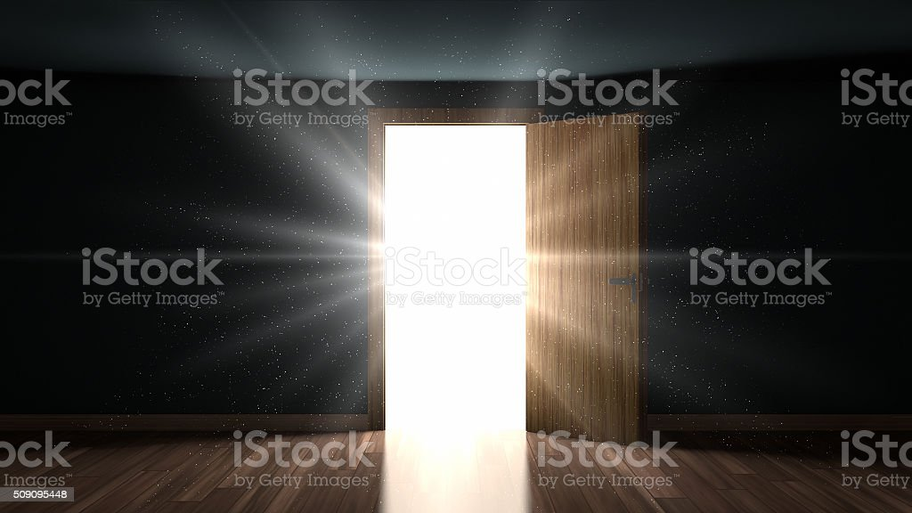 Light and particles in a room through the opening door stock photo