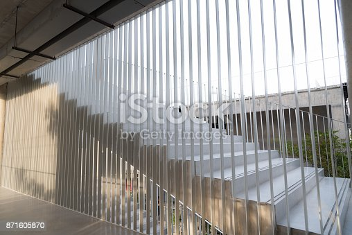 istock Light and shadows of white iron bar projected onto the white stairway. 871605870
