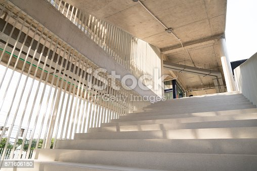 istock Light and shadows of white iron bar projected onto the white stairway. 871606180