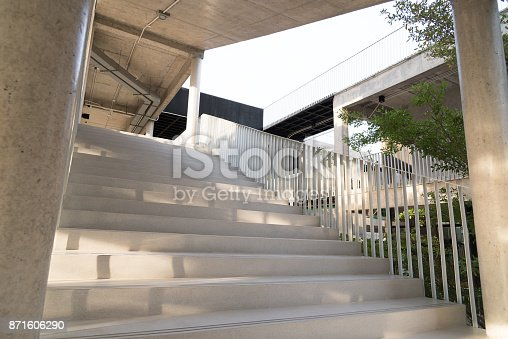 istock Light and shadows of white iron bar projected onto the white stairway. 871606290