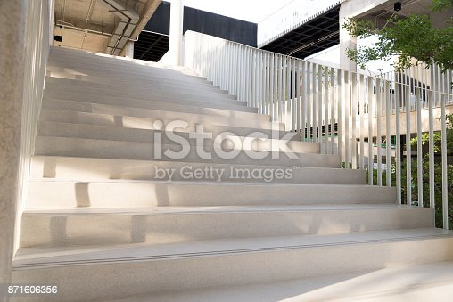 istock Light and shadows of white iron bar projected onto the white stairway. 871606356