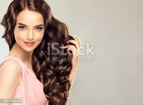 Light, tender smile on the face of young, brown haired woman  with voluminous hair.Beautiful model with long, dense, curly hairstyle , vivid makeup and magnetic look. Perfect dense, wavy,and shiny hair. Hairdressing art, hair care and beauty products.