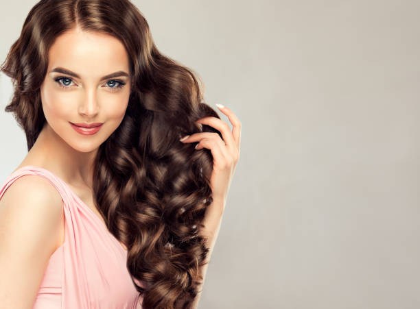 light and tricky smile on the face of young, brown haired beautiful model with long,  curly, well groomed hair. excellent hair waves. hairdressing art and hair care. - thick stock pictures, royalty-free photos & images