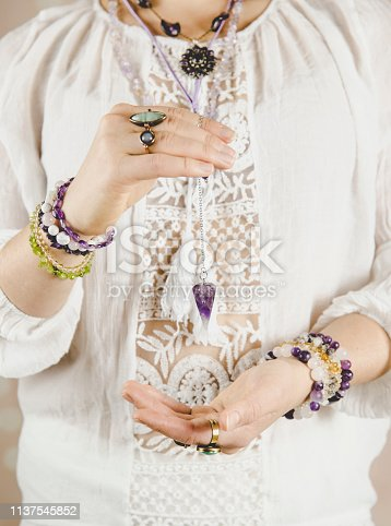 istock Light angel magic clairvoyant using pendulum, reading palm to get answers. Talking with spirits concept. 1137545852