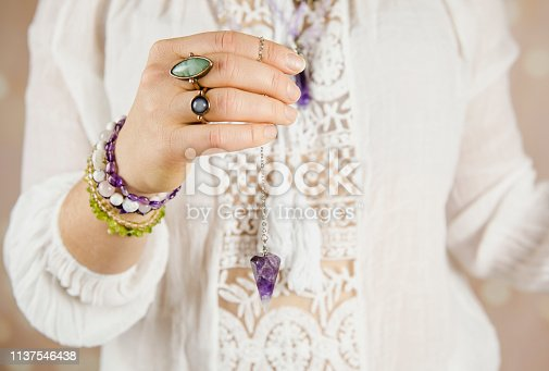 istock Light angel magic clairvoyant using pendulum, reading palm to get answers. Talking with spirits concept. 1137546438