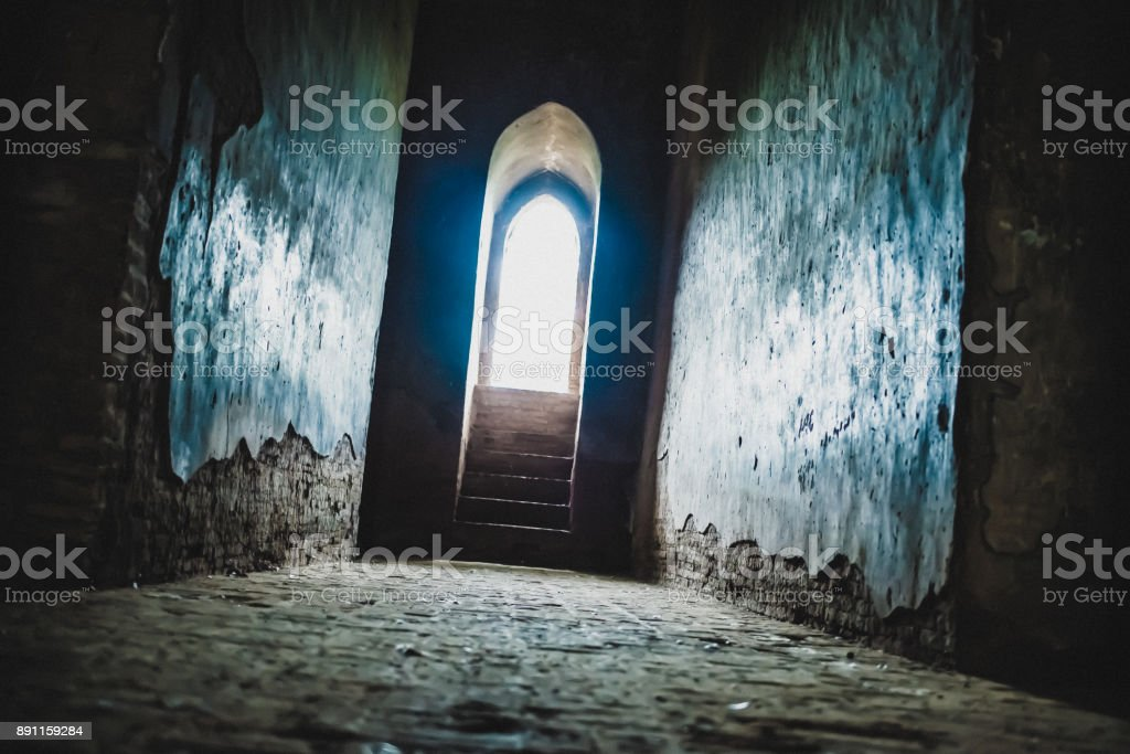 Light at the end of the tunnel concept - wide angle corridor inside a temple door with light shining through stock photo