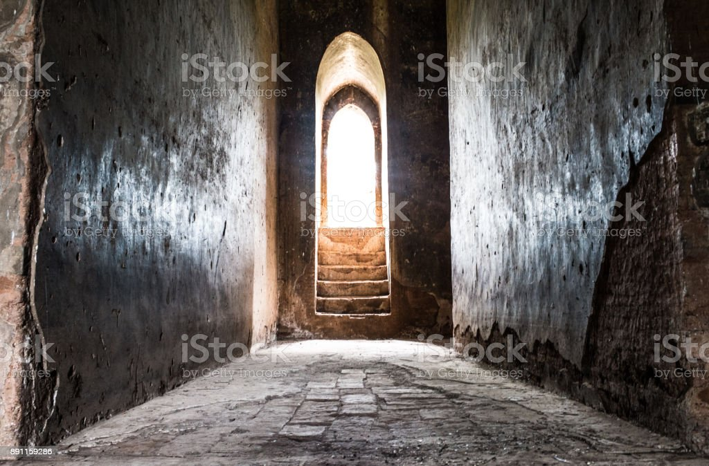 Light at the end of the tunnel concept - wide angle inside a temple door with light shining through stock photo