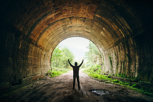 A young man stands ith arms wide open against the exit of a dark tunnel.