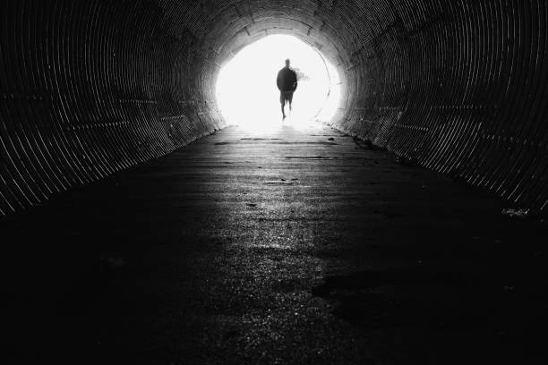 Light at the end of the tunnel with silhouette of man stock photo