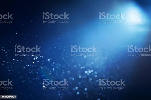Photo of Light beam and bokeh underwater at night.