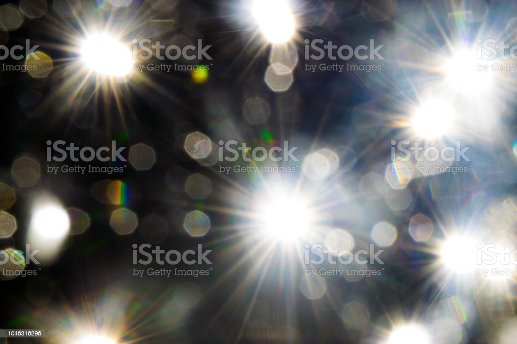 Light beams reflecting through the glass bubbles formatting the star beam shape in black background. Looks like space with the stars stock photo