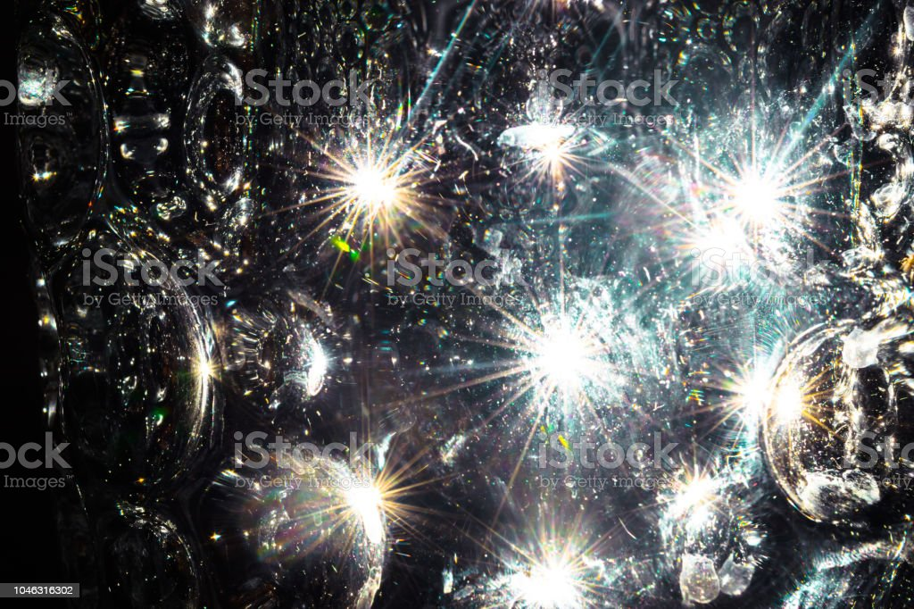Light beams reflecting through the glass bubbles formatting the star beam shape in black background. It seems like water or ice bubbles illuminated by light stock photo