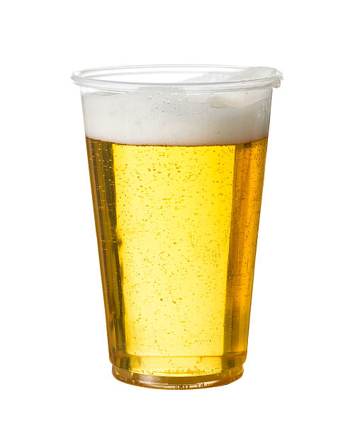 Light beer in a clear plastic cup on plain white background  stock photo