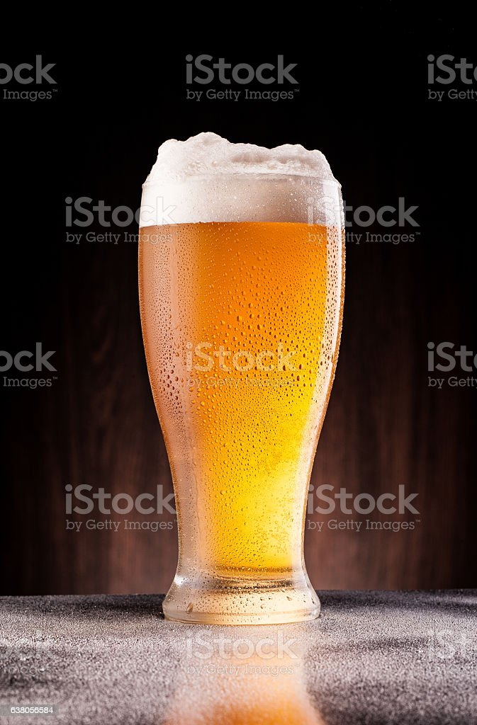 light beer in frosty glass over dark wooden background - foto de acervo