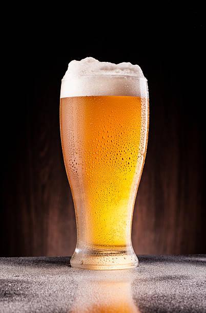 light beer in frosty glass over dark wooden background – Foto