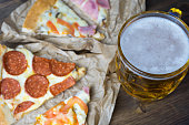 Light beer in glass and fragrant Italian pizza...