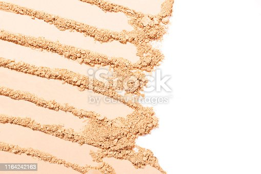 Light beige face powder smears on white background. Beauty and makeup concept.