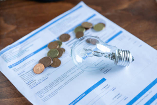Light bill with light bulb Light bill with light bulb. Conceptual about the price of electricity and paying taxes electric light stock pictures, royalty-free photos & images