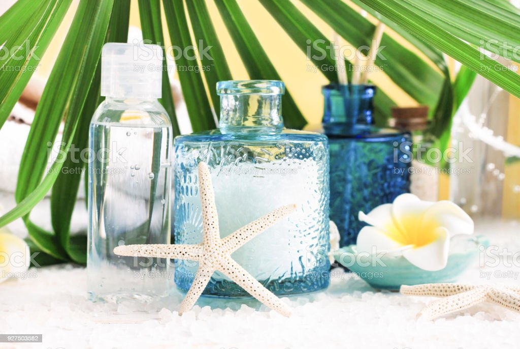 Light blue glass jar of sea salt with starfish decor, bottle of facial mineral lotion, palm leaf. stock photo