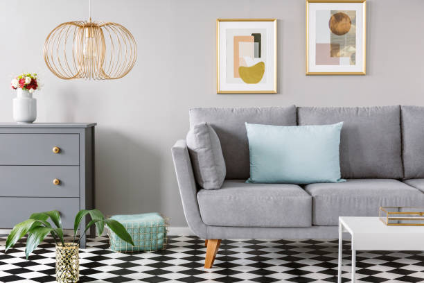 Light blue pillow placed on grey couch in bright living room interior with checkerboard linoleum floor, fresh flowers in vase on cupboard two posters hanging on the wall and gold lamp Light blue pillow placed on grey couch in bright living room interior with checkerboard linoleum floor, fresh flowers in vase on cupboard two posters hanging on the wall and gold lamp linoleum stock pictures, royalty-free photos & images